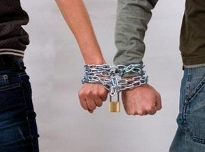 руки мужчины и женщины соединены цепью